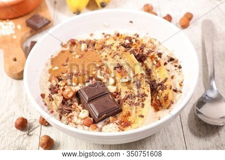 bowl of oatmeal, cereal porrdige with banana, nut and chocolate