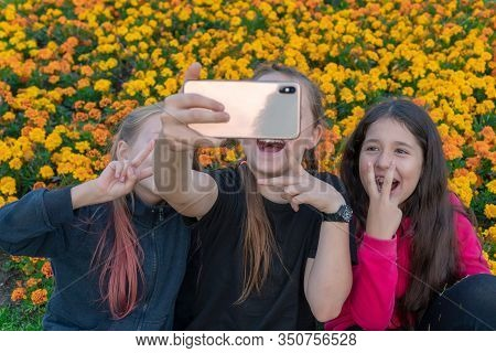 Three Teen Girls Take A Selfie On Phone On A Sunny Day And Laugh. Girls Are Showing Victory Sign Wit