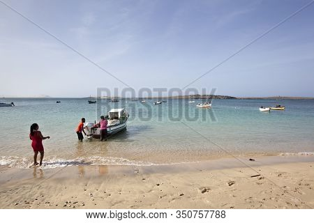 Sal Rei, Cape Verde - January 28, 2020: Two Local Men Standing In The Water Near A Small Traditional