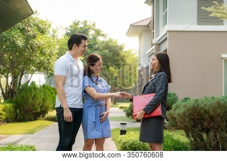 Happy Asian Couple Looking For Their New House And Shake Hands With Real Estate Broker After A Deal.