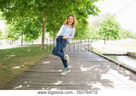Smiling Young Woman Standing On One Leg In Spring Park. Careless Lady Wearing Casual Clothing Standi