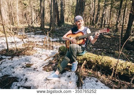 Young Woman Playing Guitar Sitting On Old Tree Covered With Moss At Sunny Spring Forest
