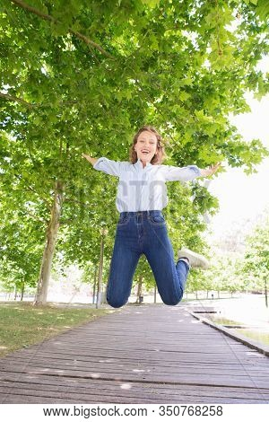 Careless Young Woman Jumping On Wooden Path In Park. Attractive Young Lady Having Fun In Sunny Sprin
