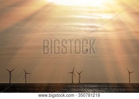 Ray Of Hope. Climate Change And Global Warming. Offshore Wind Farm Turbines Silhouetted On The Horiz
