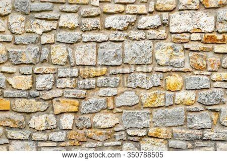 Wall Pattern Texture Background. Surface With Asymmetrical Stones. Old Wall Of Ancient Architecture.