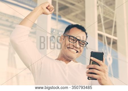Bottom View Of Smiling Young Mixed-race Man In Spectacles And White T-shirt Finishing Phone Call, Re