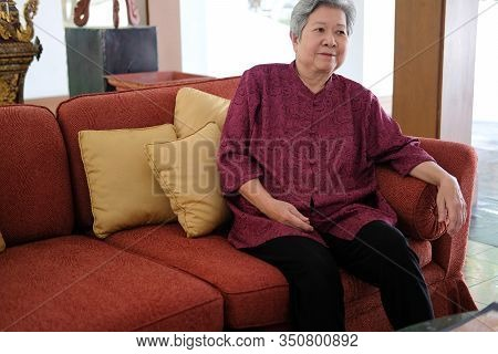 Old Elderly Senior Elder Woman Resting Relaxing On Sofa Couch In Living Room