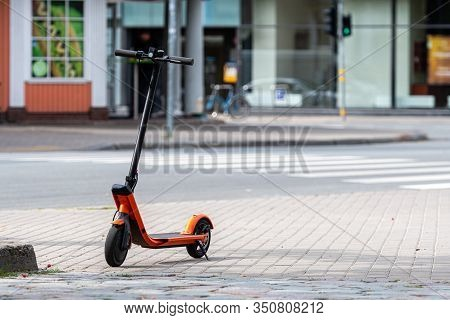 Electric Scooter Or E-scooter Parked On Sidewalk, Blurred City Street Background - Image
