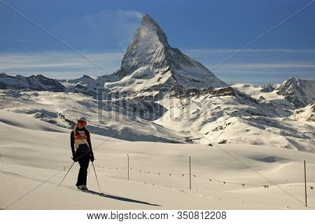 Young Woman On Ski In Colorful Clothes, Ski Helmet And Mask Standing Elegant On Untouched Snow On Ba