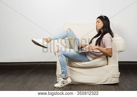 Young Woman, Sitting On A White Couch With Her Leg Up, Working On A Laptop With Her Glasses On Her H