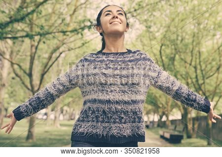 Happy Pretty Woman Spreading Hands And Walking In Park. Young Lady Wearing Sweater And Walking With