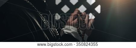 Partial View Of Catholic Priest Holding Wooden Rosary Beads Near Confessional Grille In Dark With Ra