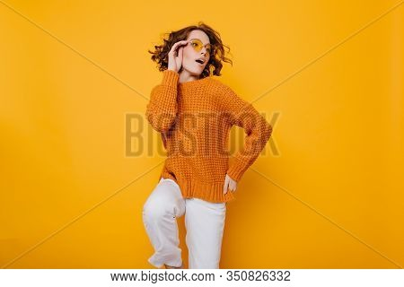 Fashionable Young Lady In Knitted Sweater And White Pants Standing On One Leg And Looking Away With