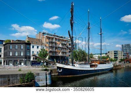 Ship moored in Willemdock in Antwerp. View of Bonapartedok harbor and vintage galleon. Antwerpen, Belgium, Europe, Flanders