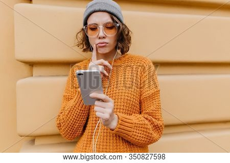 Pensive Cute Girl In Oversize Sweater Looking At Phone Screen Walking Down The Street. Outdoor Portr