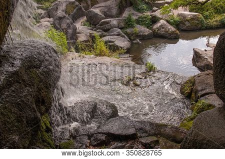 Beautiful Nature Landscape Park With Green Herbs And Trees, Big Stones And Little River With Waterfa
