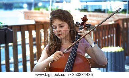 Woman Musician Playing The Cello On The Summer Terrace Outside, Intelligent Caucasian Woman Holding