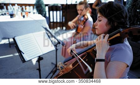 Intelligent Female Musician Plays The Cello Outdoor. Caucasian Woman Holds A Bow In One Hand And Cla