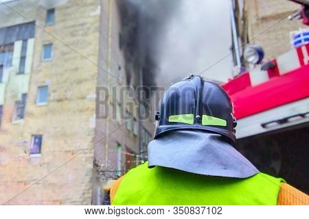 Firefighter In Front Of A Fire In A High-rise Trade Building, Fighting Fires In A Big City.