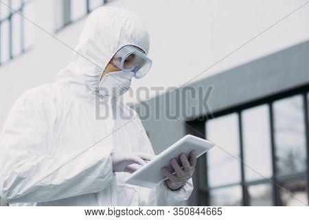 Asian Epidemiologist In Hazmat Suit And Respirator Mask Using Digital Tablet While Standing On Stree