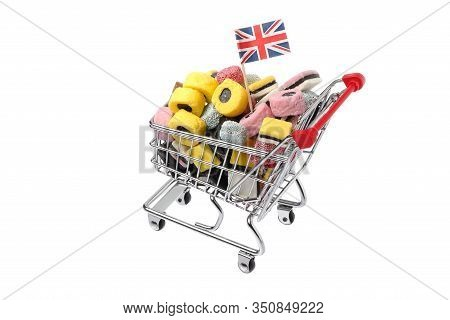 Shopping Cart Decorated With A British Flag And Filled With Assorted Licorice Candy Isolated On Whit