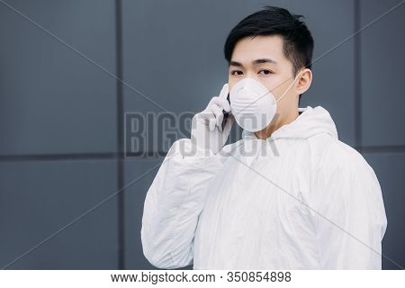 Asian Epidemiologist In Hazmat Suit And Respirator Mask Talking On Smartphone And Looking At Camera