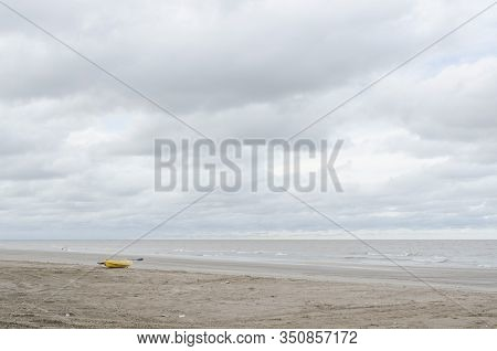Beach Landscape Without People, A Yellow Kayak In The Sand, A Calm Sea And A Cloudy Sky, In Punta Ra
