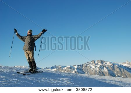 Alpine Skier Enjoying Freedom On Mountain Top