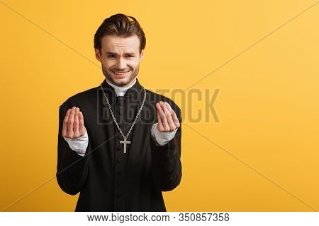 Discouraged Catholic Priest Showing Question Gesture Isolated On Yellow