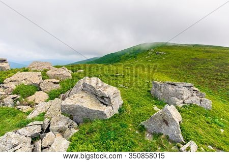 Rock On The Meadow. Cloudy Alpine Summer. Grass On The Hills, Slopes And Humps Of The Mountain