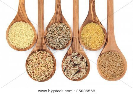 Cereal and grain selection of bulgur wheat, buckwheat, couscous, rye grain and brown and wild rice in olive wood spoons on white background.