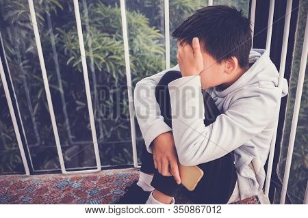 Young Asian Preteen Teenager Boy Hugging His Knee And Cover His Face And Holding A Smartphone, Cyber