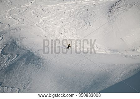 Man Freerider Gliding Down The Snowy Mountain Slope