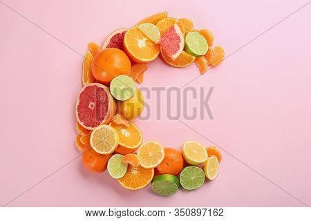 Letter C Made With Citrus Fruits On Pink Background As Vitamin Representation, Flat Lay