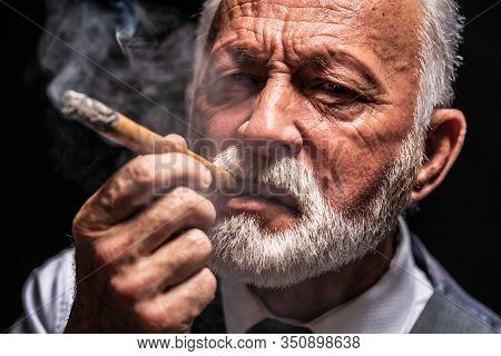 Portrait Of Serious Senior Man Who Is Smoking Cigar.