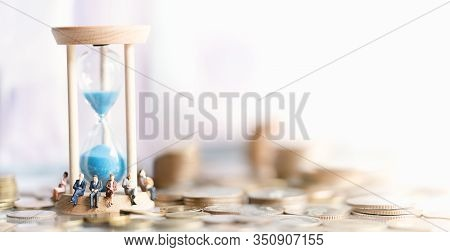 Miniature People: Elderly People Sitting On Hourglass With Coins Stack. Social Security Income And P