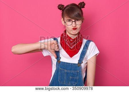 Close Up Portrait Of Unimpressed Disliking Attractive Female Student Dresses Denim Overall, White T