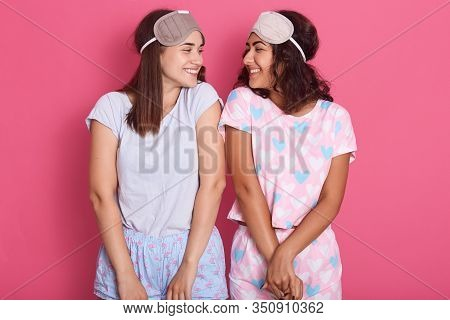 Horizontal Shot Of Attractive Young Women Standing Isolated Over Pink Background, Posing In Sleeping