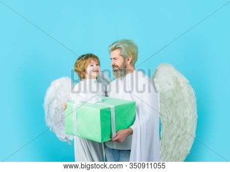 Father's Day. Little Angel Son Gives Father Gift. Happy Father In Angel Costume With Little Son Ange