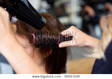 Close up of beautician's hand setting the hair properly after haircut
