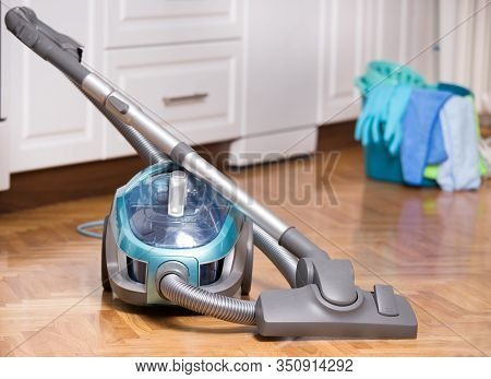 Vacuum Cleaner On Parquet Floor With Bucket And Gloves In Background. House Cleaning Concept