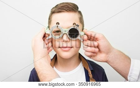 Optometrist Putting On The Boy Special Glasses To Restore Visual Acuity. Amblyopia Treatment In An O
