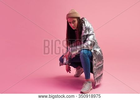 Stylish Fashionable And Modern Young Woman In A Puffy Light Down Jacket. The Jacket Is A Silver Meta