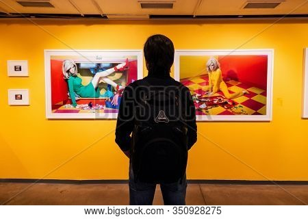Moscow, Russia - February 01, 2020: Man Looks At Photos Of Photographer Miles Aldridge At An Exhibit