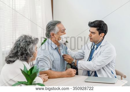 Doctor Using Stethoscope For Auscultate Asian Grandparent Patient In House, Service Life Insurance A