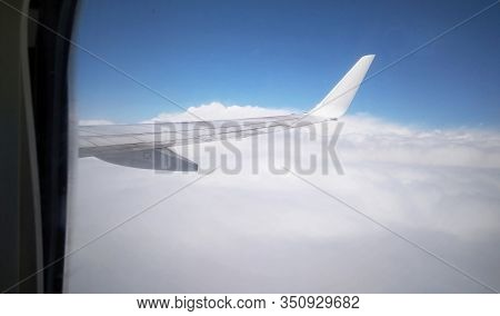 Airplane Wing From Plane Window. View From The Aircraft's Airplane To The Wing In The Sky Above The