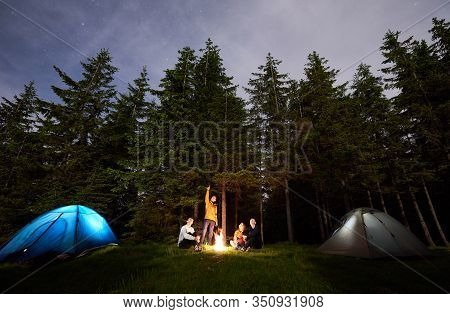 Tourist Man Showing His Friends Starry Sky Over The Camping. The Guys Are Sitting By Fire And Touris