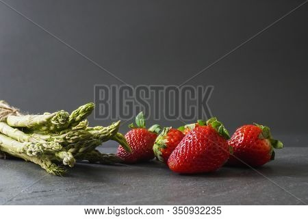 A Close-up Of A  Single Ripe Red Strawberry Rests On A Gray Slate Counter; Landscape View