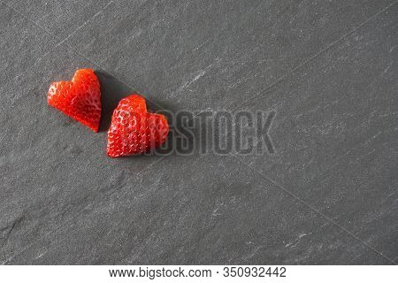 Two Red Hearts Cut Out Of Strawberries On A Gray Slate Background; Valentine's, Love