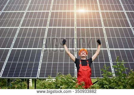 Happy Worker Man Near Solar Station Raising His Hands On A Background Of Photovoltaic Panels. Man In